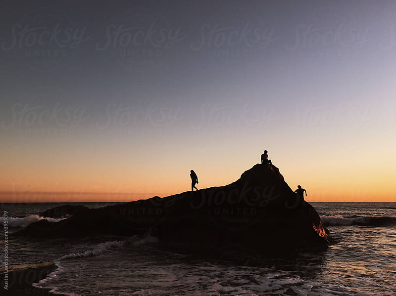 Kids playing on a rock in the ocean at sunset. by Austin Lord for Stocksy United