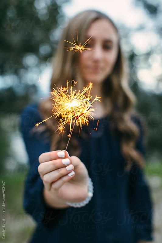 Teenage girl holding a heart shaped sparkler by Carolyn Lagattuta for Stocksy United