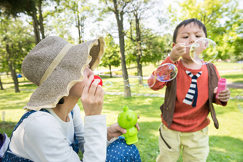 Kid and mother blowing bubbles on green grass at park by Lawren Lu for Stocksy United