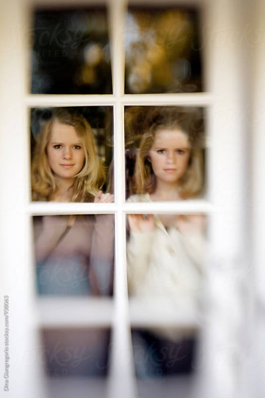 Twin Girls Looking Out Glass Door by Dina Giangregorio for Stocksy United