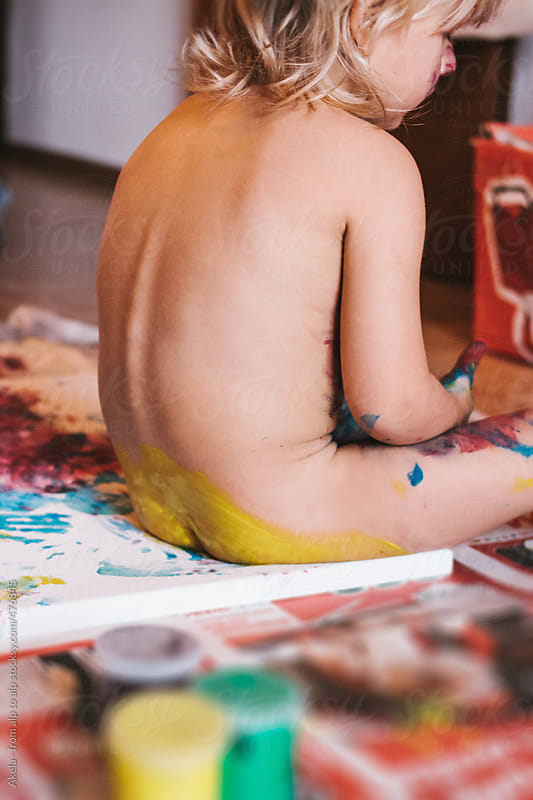 toddler painting on canvas with his butt by Leander Nardin for Stocksy United