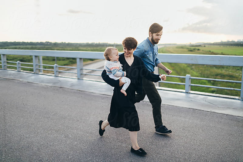 Young couple carrying their baby girl running along the road by Evgenij Yulkin for Stocksy United