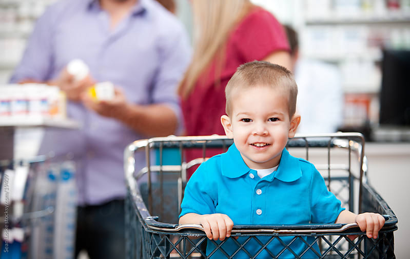Pharmacy: Happy Boy Sitting in Shopping Cart by Sean Locke for Stocksy United