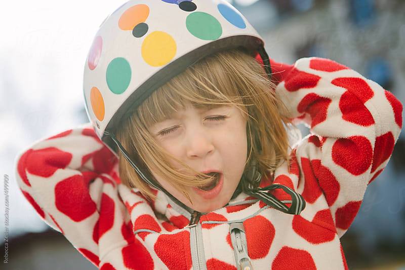 a girl with a polka-dotted helmet and jacket makes a funny face for the camera by Rebecca Zeller for Stocksy United