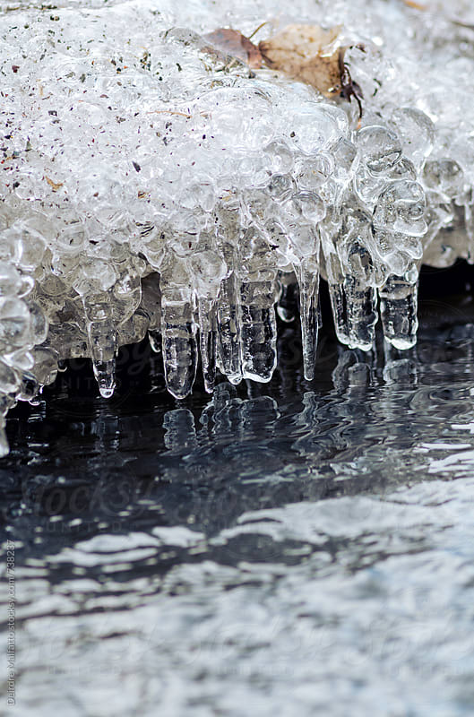 ice melting into a stream signifying the end of winter by Deirdre Malfatto for Stocksy United