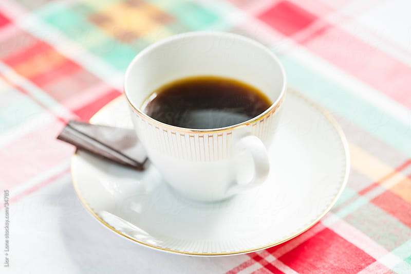 cup off black coffee on saucer with dark chocolate on checkered  by Lior + Lone for Stocksy United
