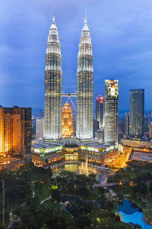 Asia, Malaysia, Selangor State, Kuala Lumpur, elevated view over the KLCC - Kuala Lumpur City Centre - urban development which includes the KLCC park, convention and shopping centre and the iconic 88 storey steel-clad Petronas Towers - illuminated at dusk by Gavin Hellier for Stocksy United
