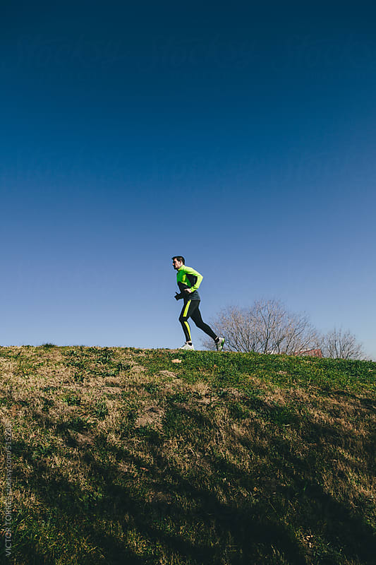 Man Running in a City Park on a Sunny Winter Day by VICTOR TORRES for Stocksy United