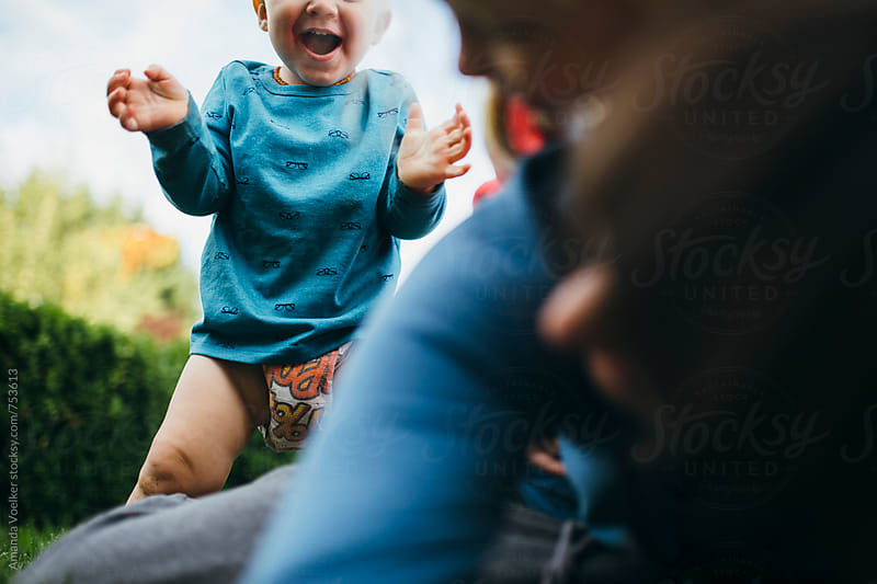 A Toddler Boy Joyfully Walks Towards His Mom and Sister playing on the ground by Amanda Voelker for Stocksy United