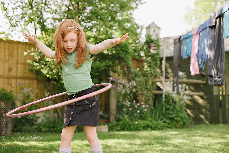 Little girl playing with a hula hoop in her garden by Craig Holmes for Stocksy United