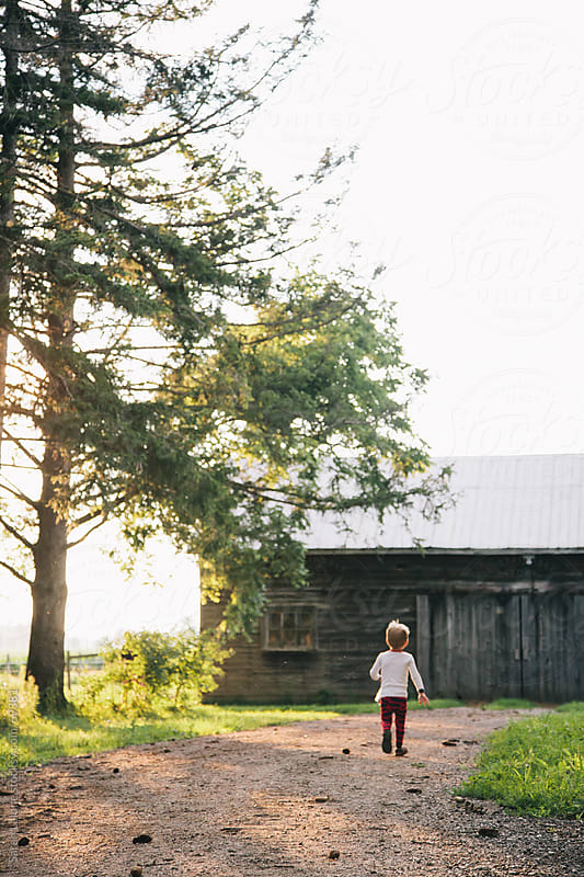 a little boy running down a lane way towards a barn by Sarah Lalone for Stocksy United
