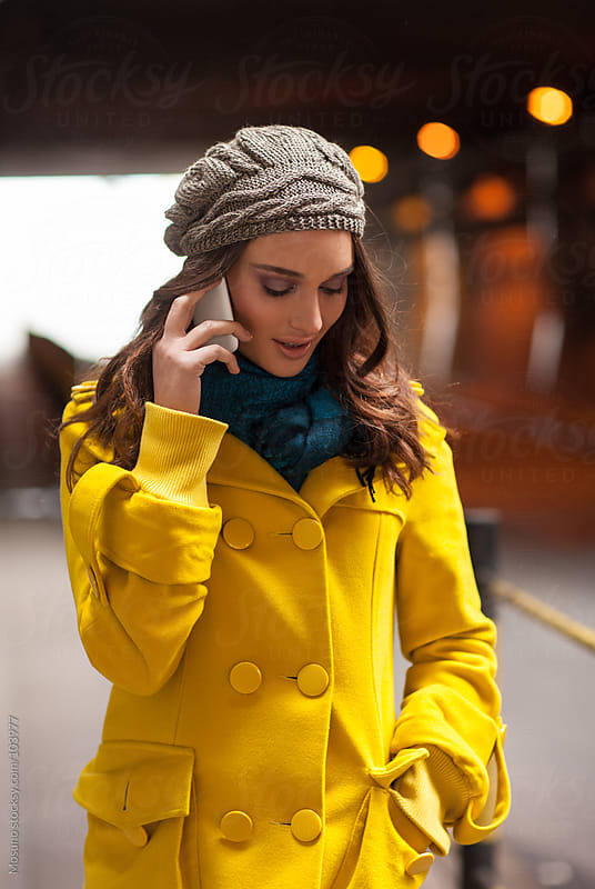 Woman in a Yellow Coat Talking on the Phone by Mosuno for Stocksy United