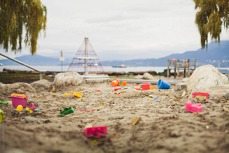 Playground sandbox left littered with toys. by Cherish Bryck for Stocksy United