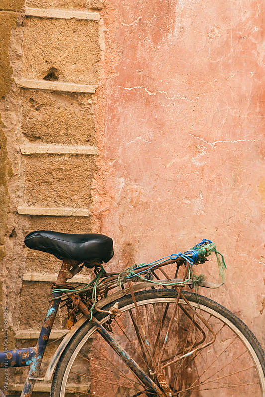 A rusty bicycle leant on a sandstone wall in Morocco  by Maresa Smith for Stocksy United