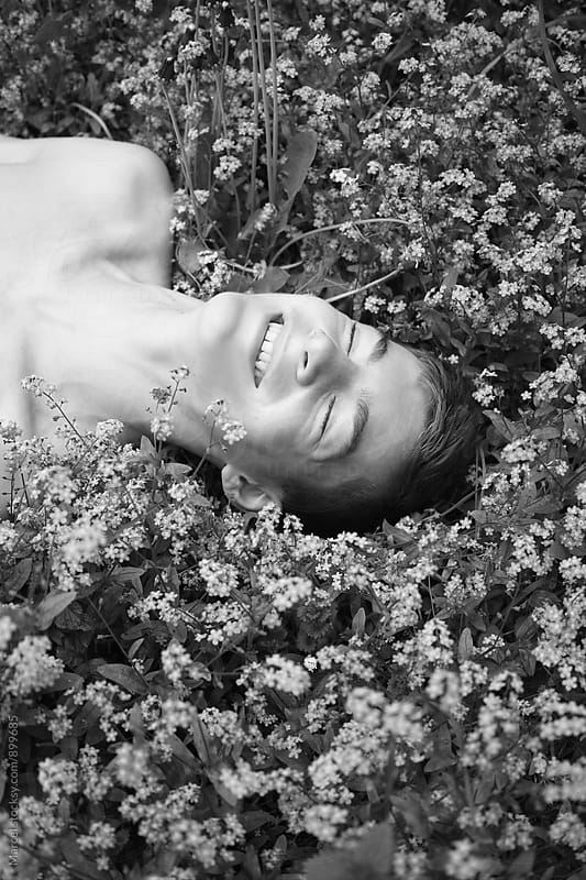 Happy boy lying between flowers by Marcel for Stocksy United