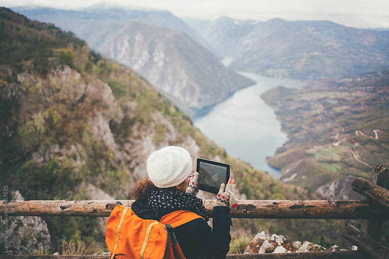 Woman With a Backpack Photographing a Landscape With a Tablet by Lumina for Stocksy United