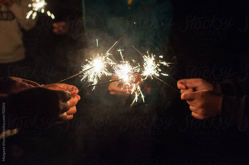 group of hands with sparklers by Margaret Vincent for Stocksy United