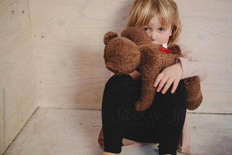 Cute young toddler girl hiding - sitting on wood floor with teddy bear by Rob and Julia Campbell for Stocksy United