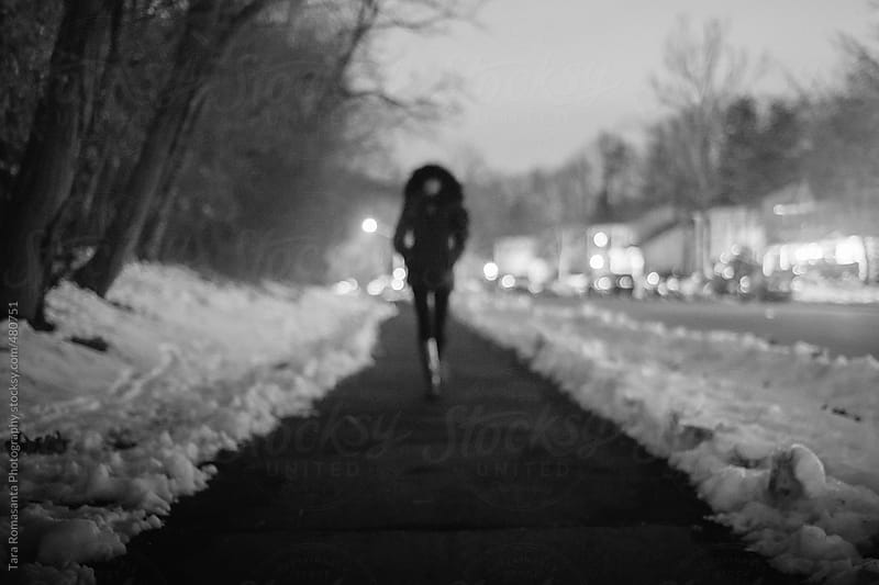 female figure walking on cold winter night by Tara Romasanta for Stocksy United