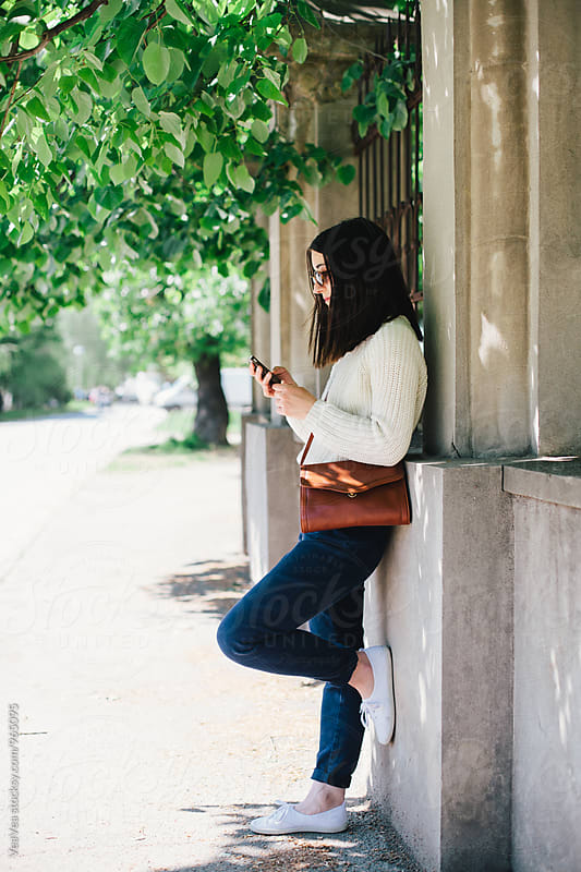 Woman using mobile phone in the street by VeaVea for Stocksy United