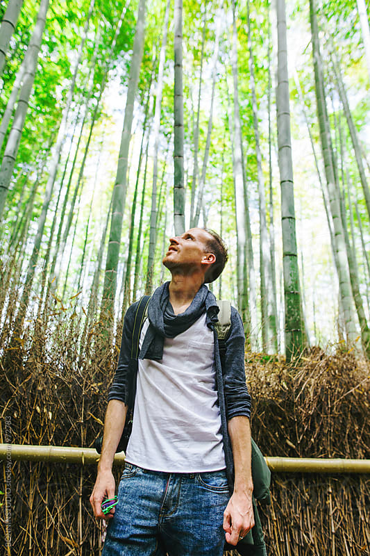 Portrait of a tourist man looking the bamboo forest. by BONNINSTUDIO for Stocksy United