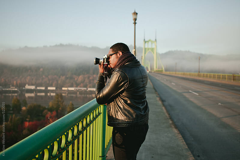 Man holding a film camera looking towards sunrise by Kristine Weilert for Stocksy United
