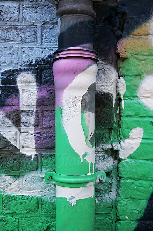 Graffiti on drainpipe & wall by Marcel for Stocksy United