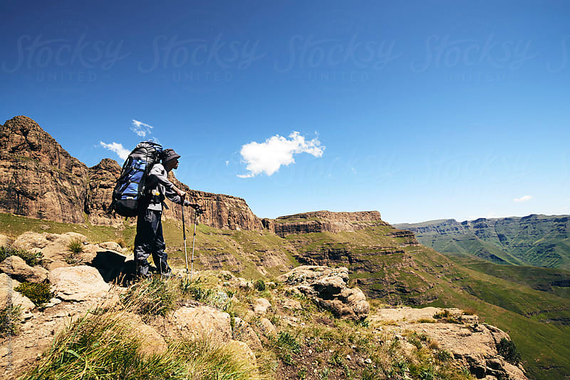 Male hiker with backpack and walking sticks taking a moment to enjoy the mountainous view.Male, hiker, hiking, mountainous, mountains, back pack, backpacking, adventure, tarvel, traveller, outdoors, outdoorsy, scenic, nature, wonder, wonderlust, healthy, by Jacques van Zyl for Stocksy United