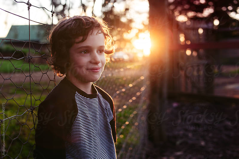 Boy standing against a fence at sunset by Angela Lumsden for Stocksy United