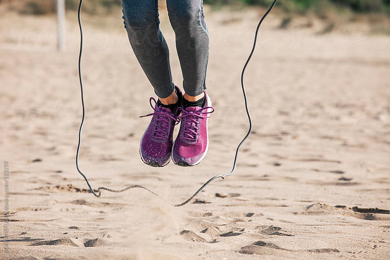 Close up of woman legs jumping rope on a beach sand. by BONNINSTUDIO for Stocksy United