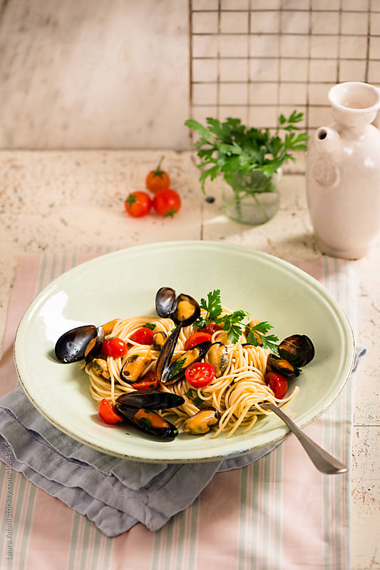 Spaghetti with mussels and cherry tomatoes by Laura Adani for Stocksy United