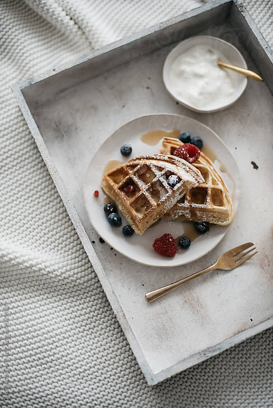 Waffles and berries with orange juice breakfast in bed by Daring Wanderer for Stocksy United