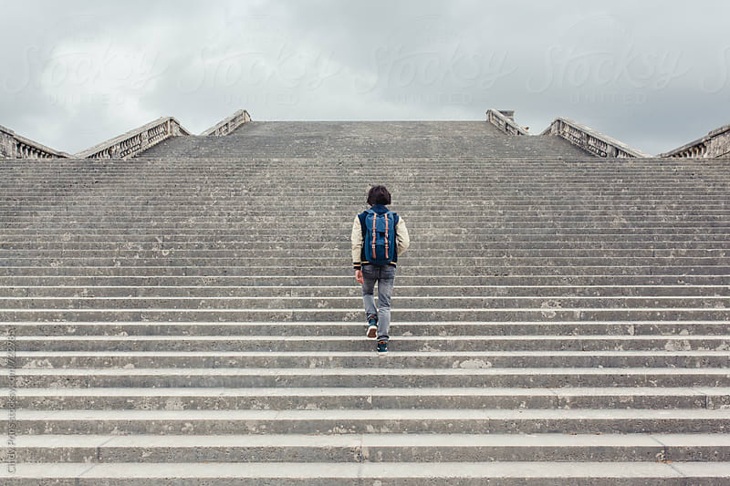Teenage boy with a backpack walking up some very big stone stairs by Cindy Prins for Stocksy United
