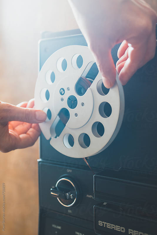 Person placing a reel on a reel-to-reel tape recorder by Pixel Stories for Stocksy United