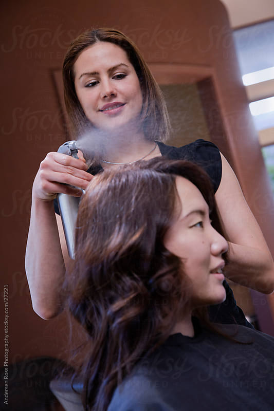 Styalist applying product to customers hair at salon by Andersen Ross Photography for Stocksy United