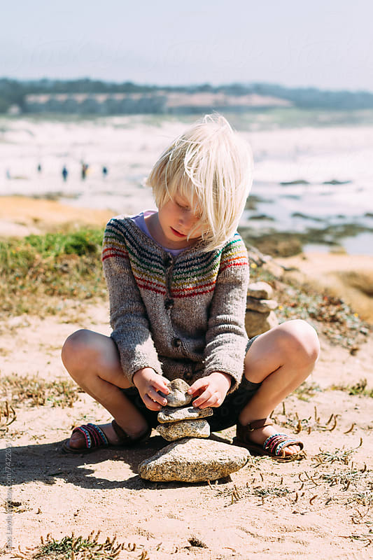 cute girl placing a stone on a cairn by Jess Lewis for Stocksy United