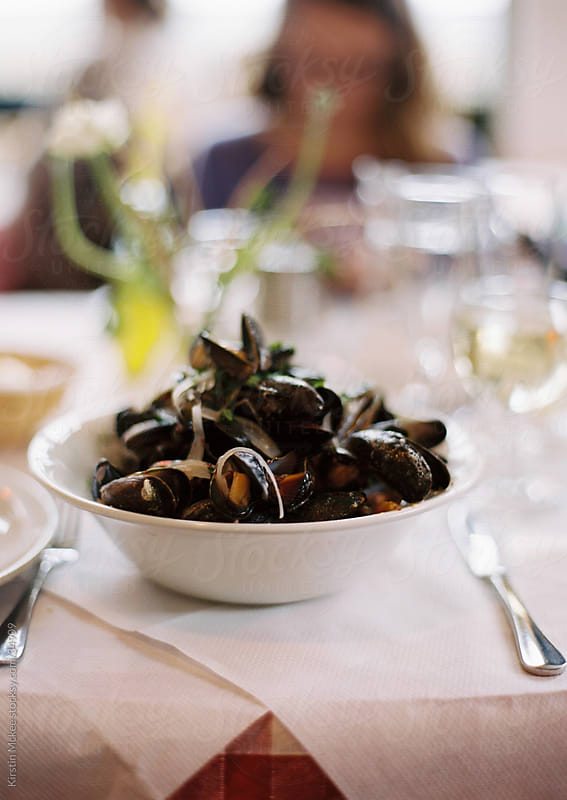 A bowl of mussels on a table by Kirstin Mckee for Stocksy United