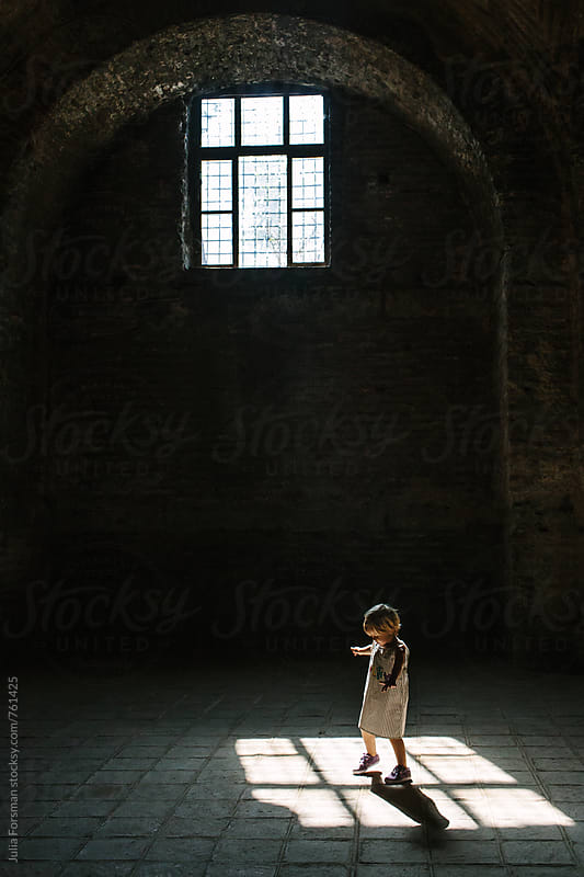 Little girl in a simple cotton dress twirls in light on the floor of a historical building. by Julia Forsman for Stocksy United