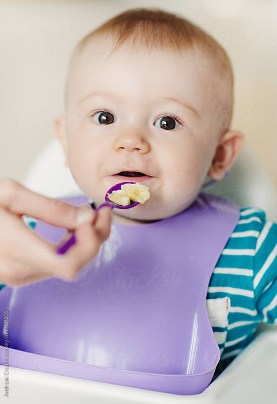 small baby boy eating banana pieces by Andreas Gradin for Stocksy United