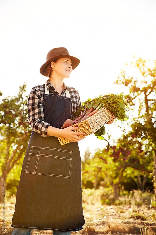Woman farmer holding organic veggies on a farm by Trinette Reed for Stocksy United