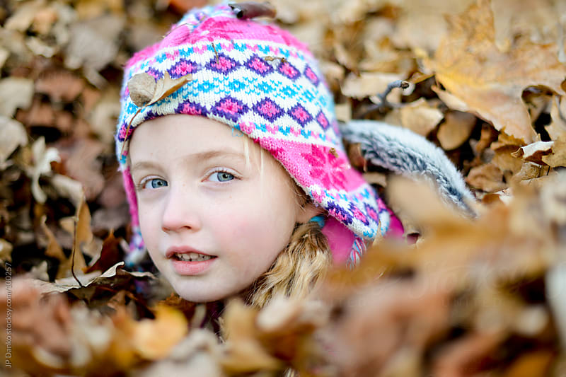 Portrait of Little Girl Playing In Fall Leaf Pile in Autumn by JP Danko for Stocksy United