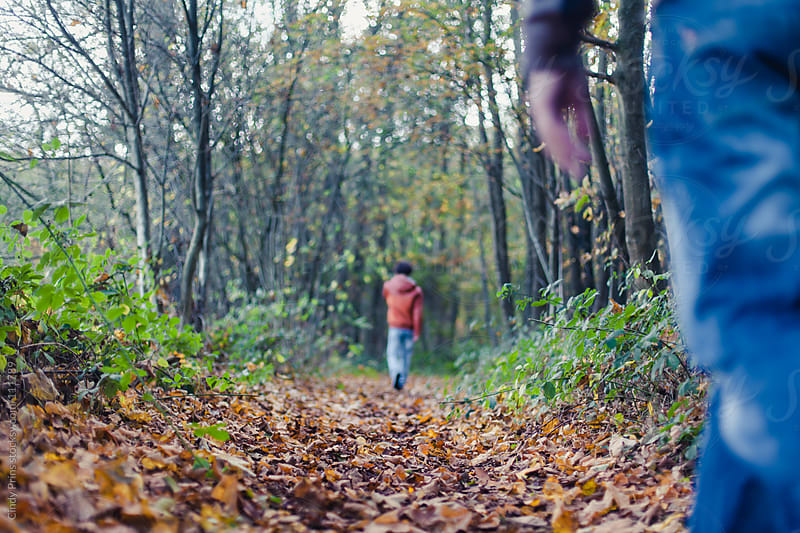 Teenager in orange jacket from the back walking in the woods with someone watching by Cindy Prins for Stocksy United