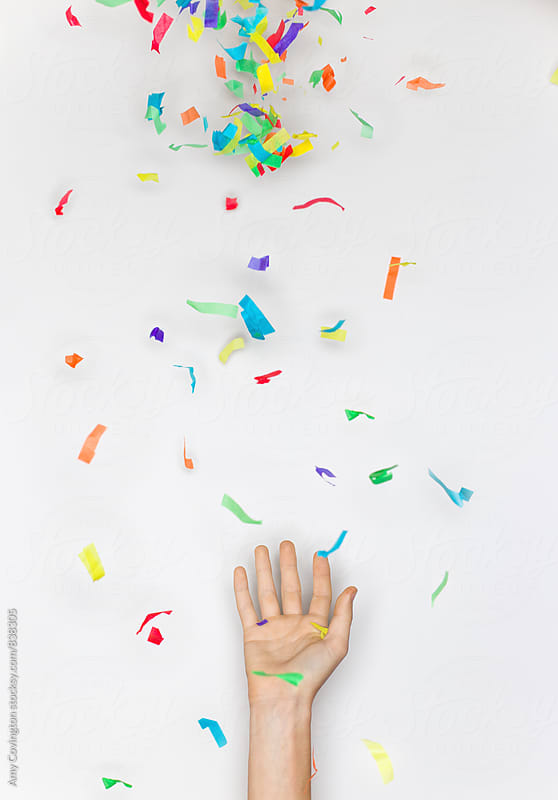 Confetti falling into an open hand by Amy Covington for Stocksy United