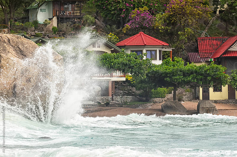 Sea Wave crashing against rock with big splash in front of bungalows at the coast by Alice Nerr for Stocksy United