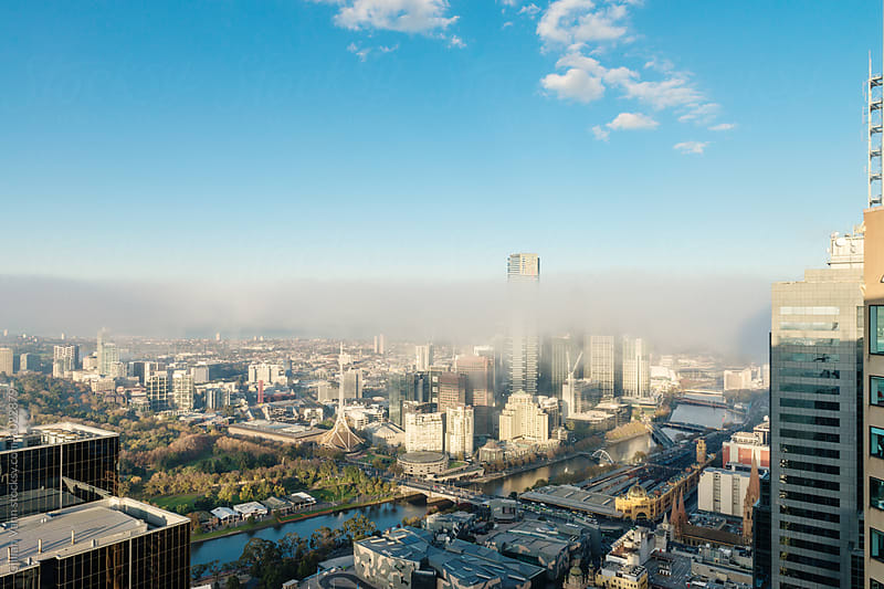 Melbourne city with a line of fog rising on a winter's morning by Gillian Vann for Stocksy United