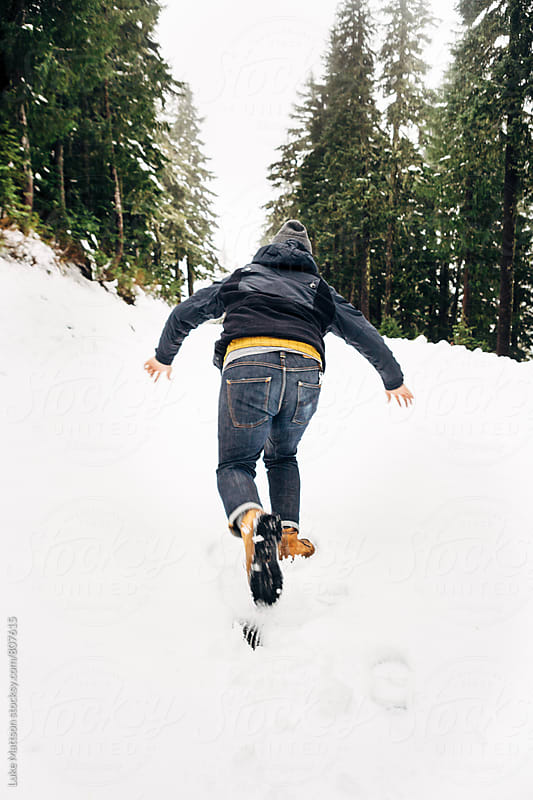 Man Slipping And Falling Forward In Snow Surrounded By Pine Forest by Luke Mattson for Stocksy United