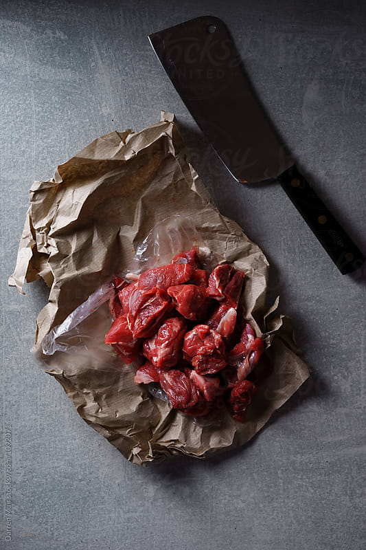Fresh diced beef in butchers paper and a meat cleaver on stone background. by Darren Muir for Stocksy United