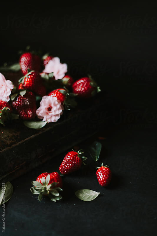 Strawberries and flowers on a dark background by Natasa Kukic for Stocksy United