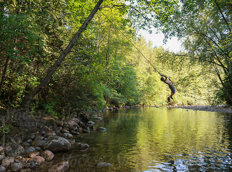 Boy On Rope Swing Over Creek by Ronnie Comeau for Stocksy United