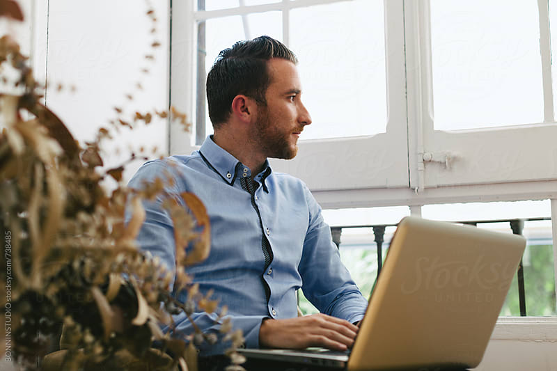 Entrepreneur man using his laptop at office. by BONNINSTUDIO for Stocksy United